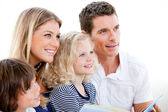 United family reading a book — Stock Photo