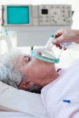 Senior patient receiving oxygen mask — Stock Photo