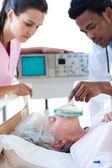 Medical team resuscitating a senior patient — Stock Photo