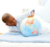 Cute little boy playing with a terrestrial globe — Stock Photo