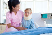 A nurse looking after a petient wih a neck brace — Stock Photo
