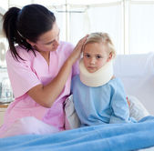 A nurse looking after an upset girl with a neck brace — Stock Photo
