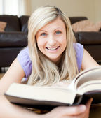Smiling woman reading a book — Stockfoto