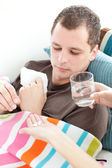 Sick man taking medicine on the sofa — Stock Photo