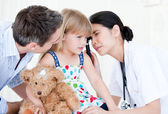 Radiant female doctor examining little girl with medical equipme — Stock Photo