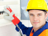 Smiling electrician repairing a power plan — Stock Photo