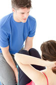 Young woman doing sit-ups assited by her personal trainer — Stock Photo