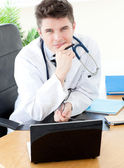 Smiling male doctor using a laptop sitting at his desk — Stock Photo
