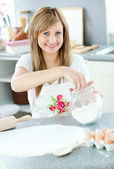 Portrait of a cheerful woman preparing a cake in the kitchen — Stock Photo