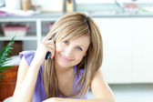 Portrait of a cheerful woman using a phone in the kitchen — Stock Photo