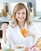 Young woman having breakfast in the kitchen — Stock Photo