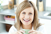 Cheerful woman holding a cup of tea in the kitchen — Stock Photo