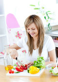 Cheerful woman preparing a healthy meal in the kitchen — Stock Photo