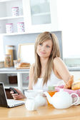 Cheerful woman using a phone and laptop in the kitchen — Stock Photo