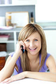 Cheerful woman answering the phone in the kitchen — Stock Photo