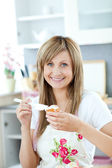 Delighted woman preparing a breakfast in the kitchen — Stock Photo
