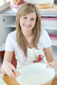 Bright woman preparing a cake in the kitchen — Stock Photo