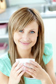 Confident woman holding a cup of coffee in the kitchen — Stock Photo