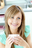 Self-assured woman holding a cup of coffee in the kitchen — Stock Photo