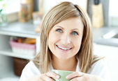 Happy woman holding a cup of coffee in the kitchen — Stock Photo