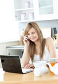 Delighted woman using a laptop in the kitchen — Stock Photo