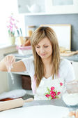 Smiling woman preparing cakes in the kitchen — Stock Photo