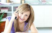 Mulher sorridente, usando um telefone na cozinha — Foto Stock