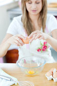 Smiling woman preparing eggs in the kitchen — Stock Photo