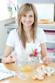 Delighted woman preparing a cake in the kitchen — Stock Photo
