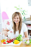 Young woman preparing a salad in the kitchen — Stock Photo