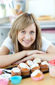 Delighted woman eating cakes in the kitchen — Stock Photo