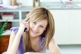 Delighted woman talking on the phone in the kitchen — Stock Photo