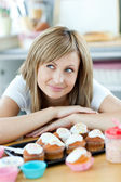 Delighted woman wants to eat cakes in the kitchen — Stock Photo