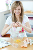 Pretty woman preparing a cake in the kitchen — Stock Photo
