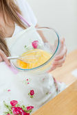 Close-up of a teen woman preparing a cake in the kitchen — Stock Photo
