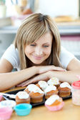 Delighted woman looking at cakes in the kitchen — Stock Photo