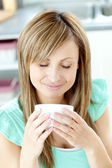 Delighted woman holding a cup of coffee in the kitchen — Stock Photo