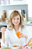 Delighted woman having breakfast in the kitchen — Stock Photo