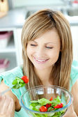 Young woman eating a salad in the kitchen — Stock Photo