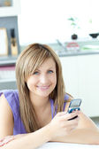 Teen woman sending a text in the kitchen — Foto Stock