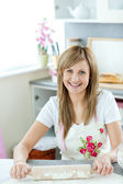 Portrait of a delighted woman preparing a cake in the kitchen — Stock Photo