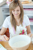 Portrait of a happy woman preparing a cake in the kitchen — Stock Photo