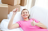 Positive woman relaxing on a sofa with boxes — Stock Photo