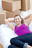 Portrait of a cute woman relaxing on a sofa with boxes — Stock Photo