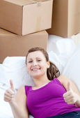 Portrait of a radiant woman relaxing on a sofa with boxes — Stock Photo