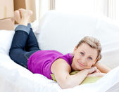 Portrait of a joyful woman relaxing on a sofa with boxes — Stock Photo
