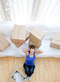 Tired woman sitting between boxes — Stock Photo