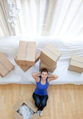Exhausted woman sitting between boxes at home — Stock Photo