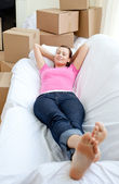 Donna affascinante e rilassante su un divano con scatole — Foto Stock