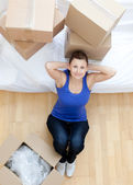 Relaxed woman sitting between boxes at home — Stock Photo